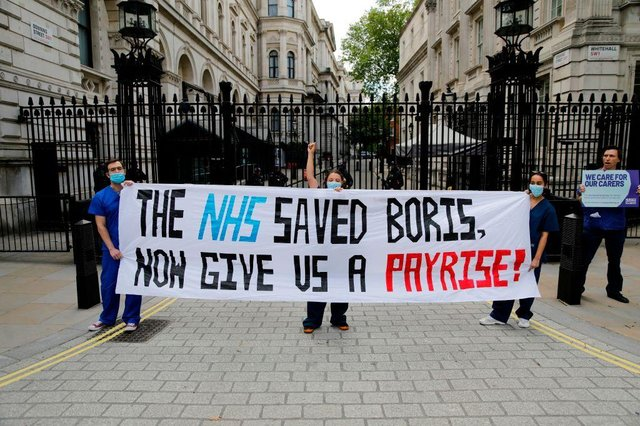 Nurses who work at central London hospitals protest with placards outside Downing Street on May 13, calling for improved conditions and pay for nursing staff on the occasion of International Nurses Day 2020 during the COVID-19 pandemic (Photo: TOLGA AKMEN/AFP via Getty Images)