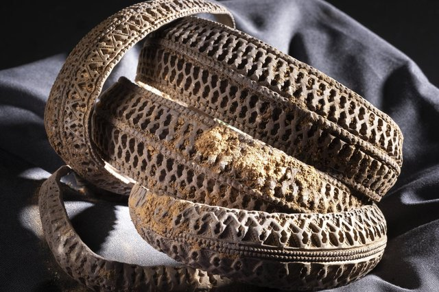 Four annular silver 'ribbon bracelet' arm-rings held together at the terminals by a silver Hiberno-Norse broad-band which has been looped around to hold them all in place, from the Viking age Galloway Hoard